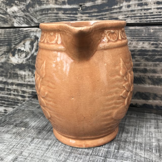 This wonderful McCoy water lily pitcher dates to the 1930s. It is a lovely terra cotta color, detailed with lotus flower...