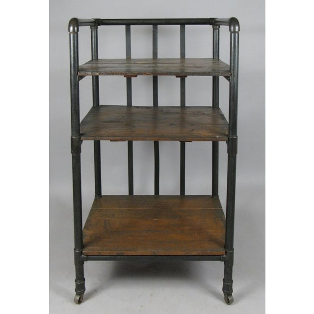 A very handsome 1950s rolling industrial cart or bookcase, with a cast iron frame and dark walnut stained shelves. Mounted...