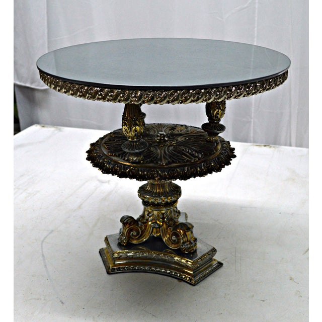 Palatial cake stand made in pewter metal with elaborated design and a shaded gold patina. Back painted gray glass top....