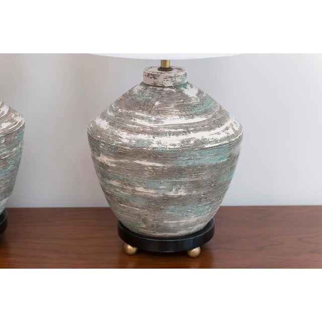 Textural ceramic lamps with brass ball feet.