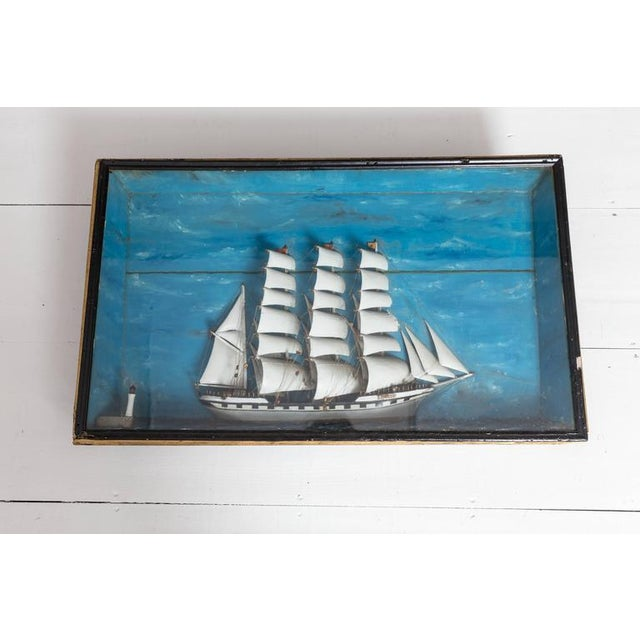 French ship diorama with a large Schooner and small lighthouse. Hand-carved out of wood which includes the hull, sails,...
