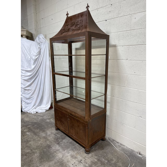 This is an unusual all metal (heavy) display cabinet. It's breaks down into three sections. The roof the center section...