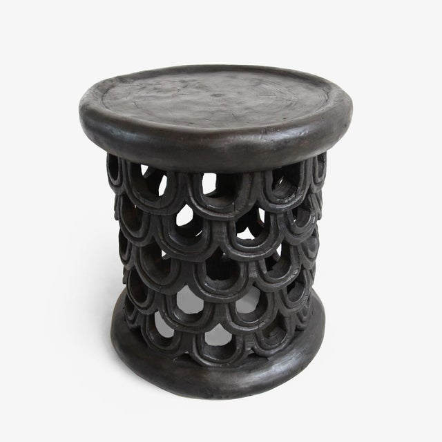 Original hand carved Bamileke small side stool. Unique pattern of carved feather or scale design with ebony stained wax...