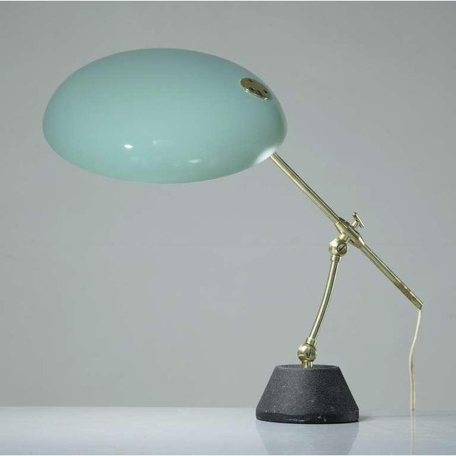 A Swiss desk lamp by/in the manner of BAG Turgi. The lamp has a green lacquered metal shade on a brass rod and cast iron...