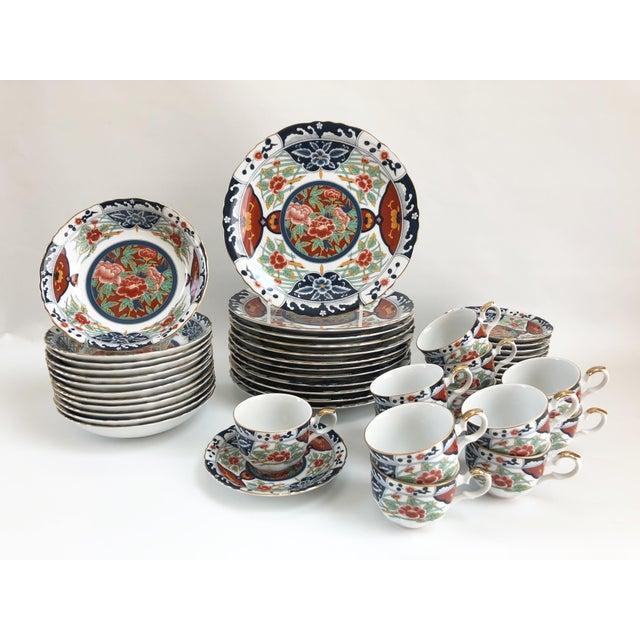 Gorgeous set of Japanese porcelain Imari-style dinner plates elaborately decorated throughout with scalloped gilt rims,...