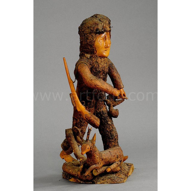 a rustic wooden hunter statue with deer. carved out of a piece of root wood. germany, black forest ca. 1920