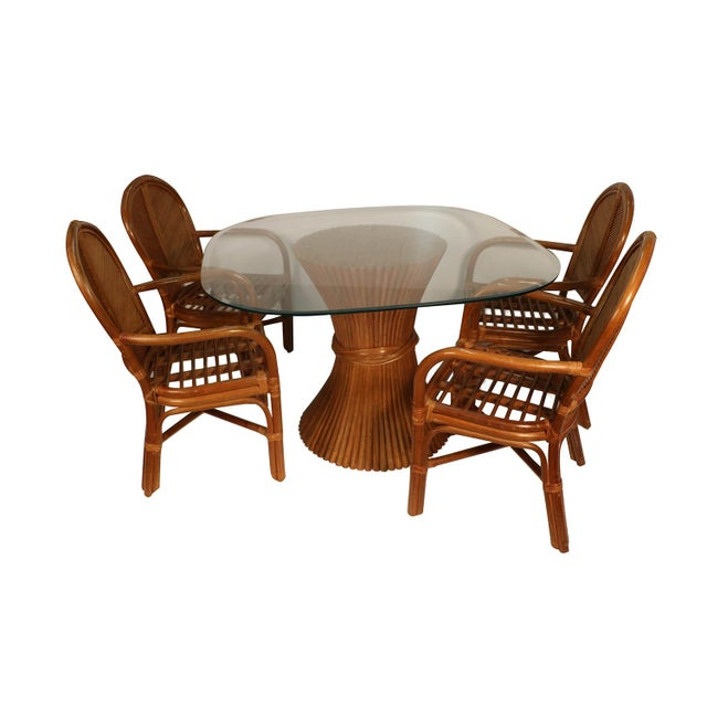 A stunning Rattan dining set in the style of McGuire Furniture. Features beveled edge square glass tabletop with rounded...