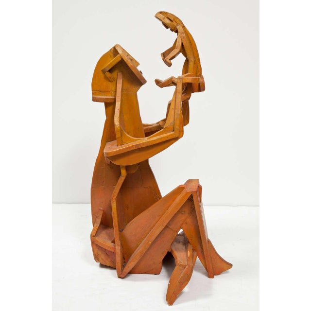 A painted and signed wood sculpture of a mother and child, beautiful in its pureness and simplicity.