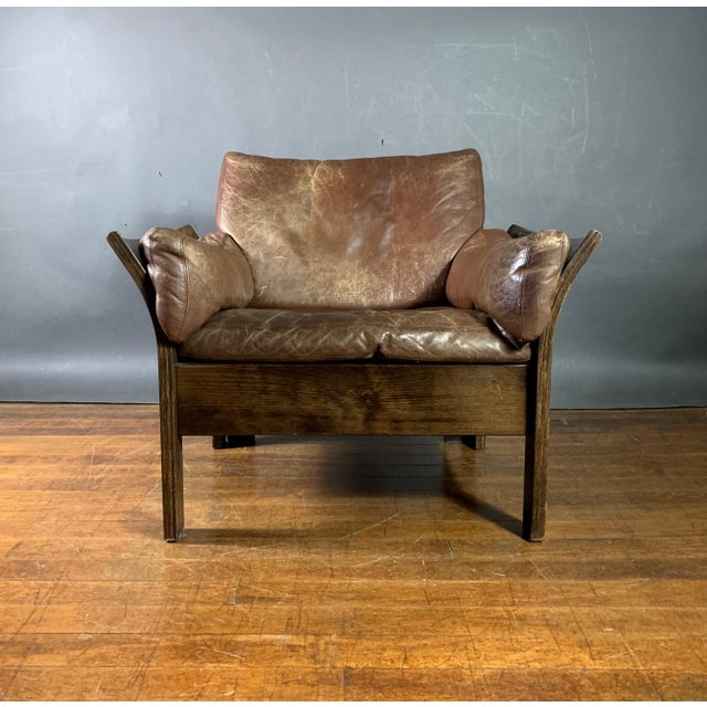 This is am incredibly comfortable lounge chair with a generous flair to the arms and rather soft medium brown leather...