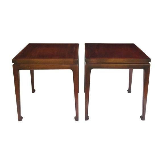 A pair of end tables in walnut with a polished lacquer finish made by Fine Arts Furniture of Grand Rapids, Michigan in...