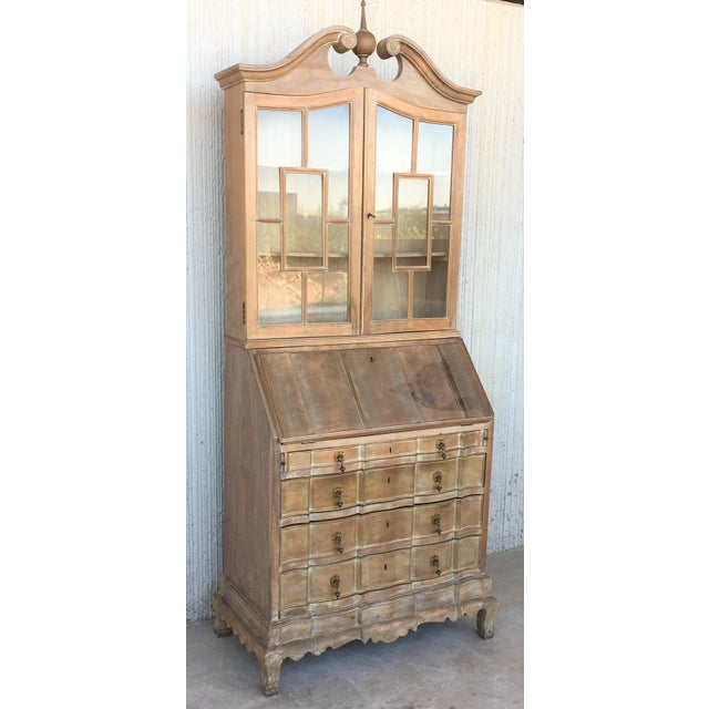 About With a broken bonnet with rosette form ends and an urn form finial. The shaped burled wood double glass door opens...