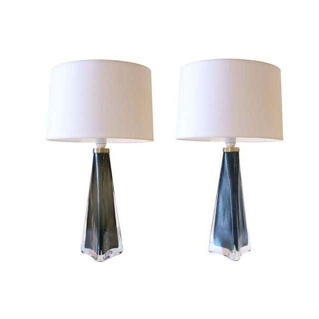 A pair of conical table lamps with polished brass hardware. Each lamp features handblown glass, one in a beautiful smokey...