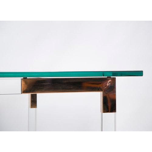 A stunning lucite and brass console table designed by Charles Hollis Jones as part of his Metric Series. A custom reverse...