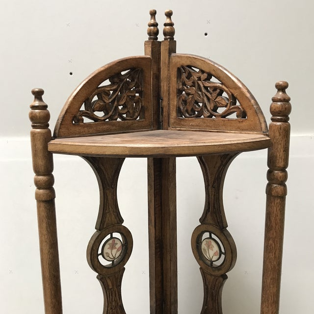 Stunning Indonesian carved corner shelf with inlaid stone detail. Three shelves, single drawer.