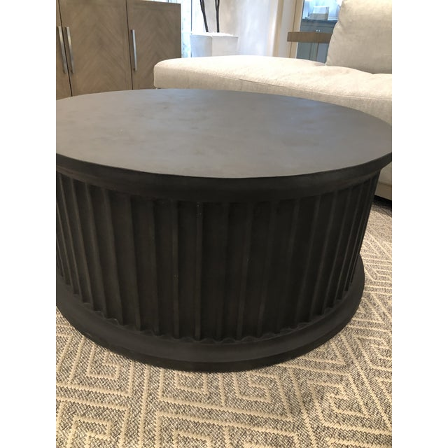 Cast concrete cocktail table in a 'basalt' finish. Round with fluted detailed along the sides. Works in transitional and...