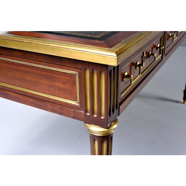Circa 1850s Louis XVI style mahogany desk has a new black leather top, brass trim and hardware, three functional drawers...