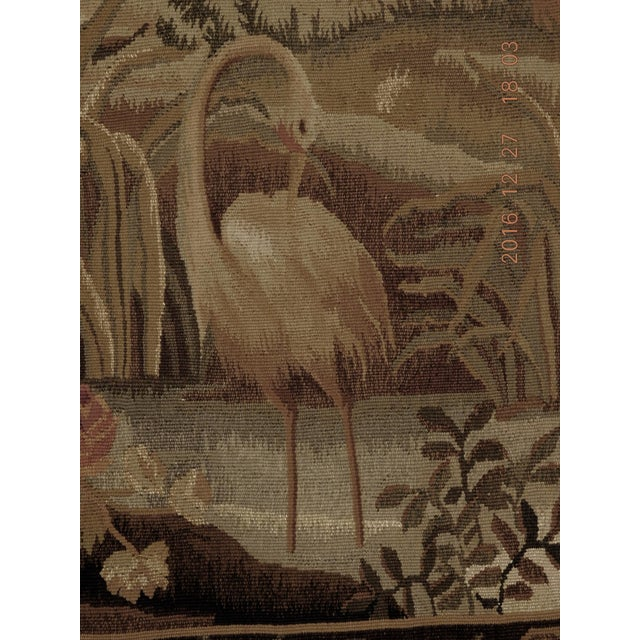 Abusson style tapestry recreated by China's artisans, depicting a landscape scenary with birds in the foreground and a...