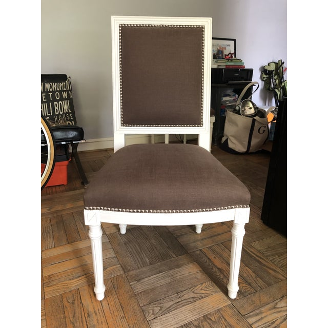 Two Jonathan Adler dining chairs with white wood, grey linen seats. Purchased at SoHo sample sale a few years ago and...