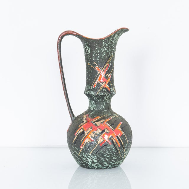 """This dark glazed pitcher has great colorful texture and shape. At 14"""" high with a refined form, delicate handle and..."""
