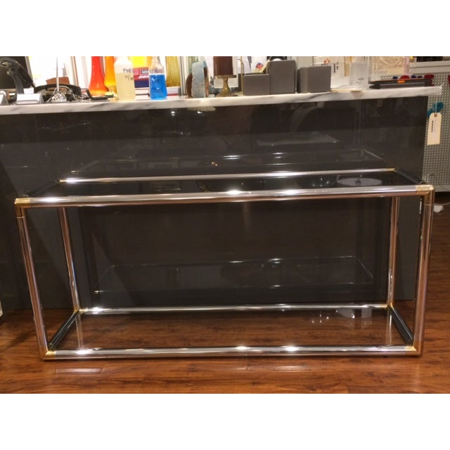 Vintage chrome and brass tubular console with two glass shelves. Sleek and timeless design!
