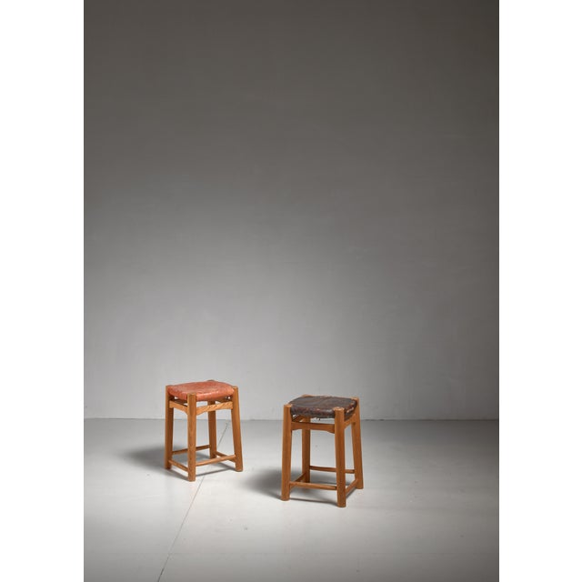 A pair of French stools with an oak frame, rush seat and a red and a brown leather seat pad. The stools are reminiscent of...