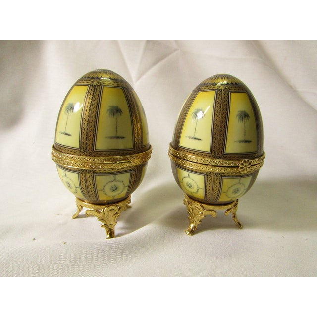 Pair of Eggs in an Art Nouveau style, with pressed gold metal trim, ornate feet and Palm tree designs on the porcelain....
