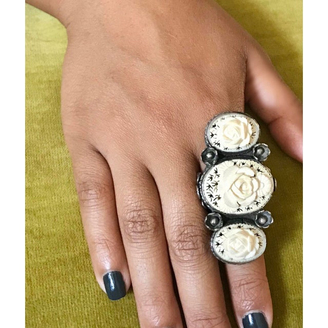 Large, artisan made ornate sterling silver ring set with three c.1930/40s hand carved bone floral motif ovals. The ring is...