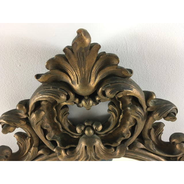 Early 20th century carved wooden rococo mirror; Circa 1920, with a gilded bronze finish, All handcarved wood. Mirror has...
