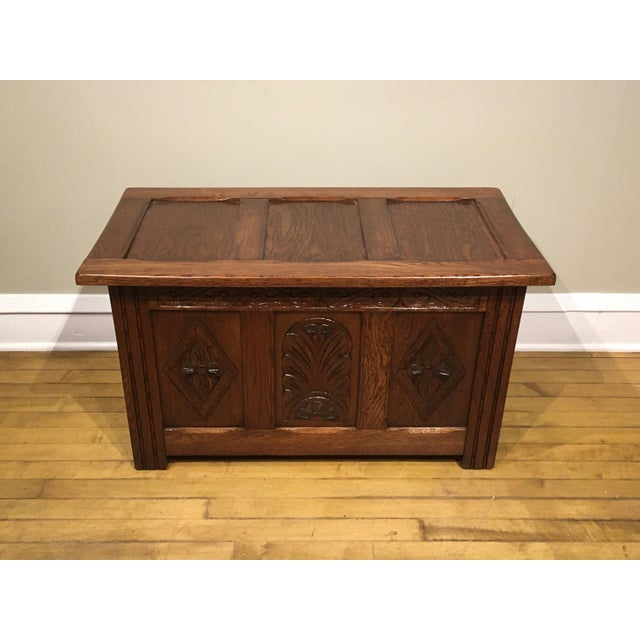 This coffer has three decorative Celtic style carved front panels with a circle inside diamond shape style carvings on the...