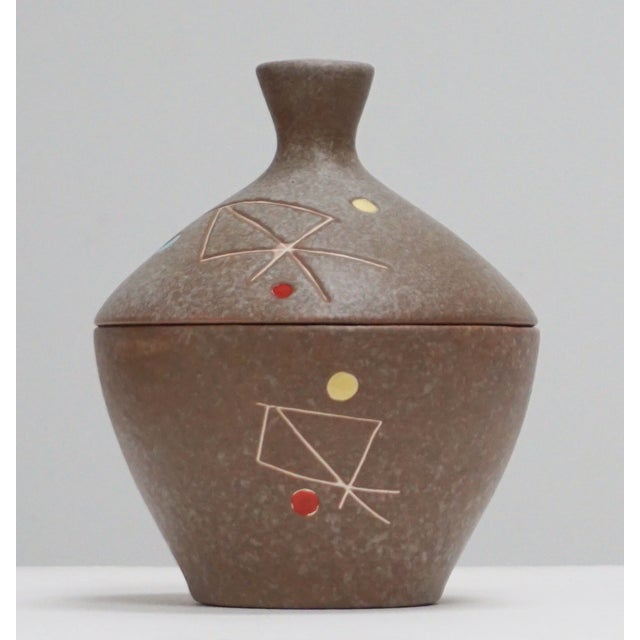 """Large brown ceramic studio pottery pot with lid. It has geometric designs and is not marked """"Gene,"""" but likely his."""