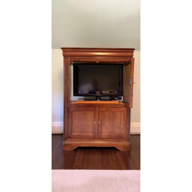 This is a meticulously crafted entertainment armoire/ cabinet. With cherry finish handmade by Grange Furniture in France....