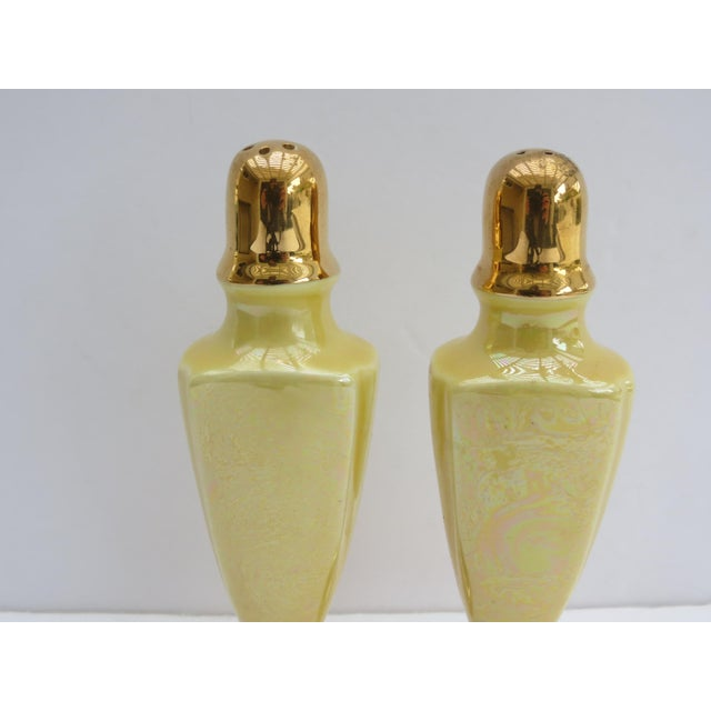 A lovely pair of iridescent yellow salt and pepper shakers with gold accents. A pretty pop of color to your table top!...