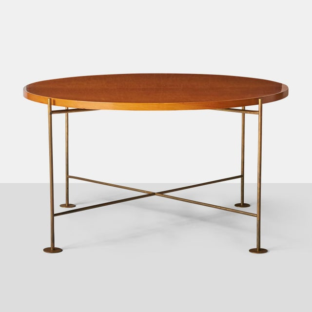 A coffee table by Raphael with X-base stretchers, France, circa 1956, made of gilded brass, birch, Lit.: G. Bloch-...
