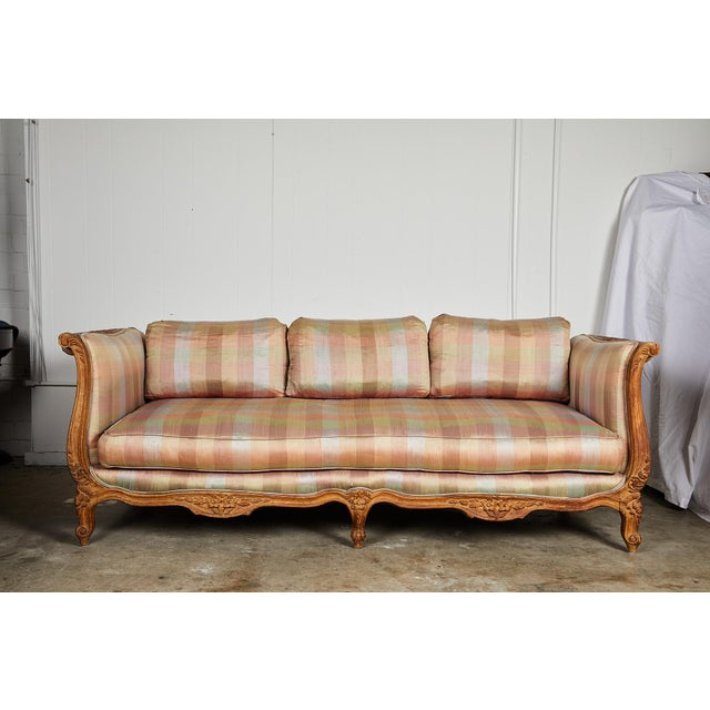 20th Century Hollywood Regency sofa or daybed influenced by the French Louis XV aesthetic featuring a pickled and carved...