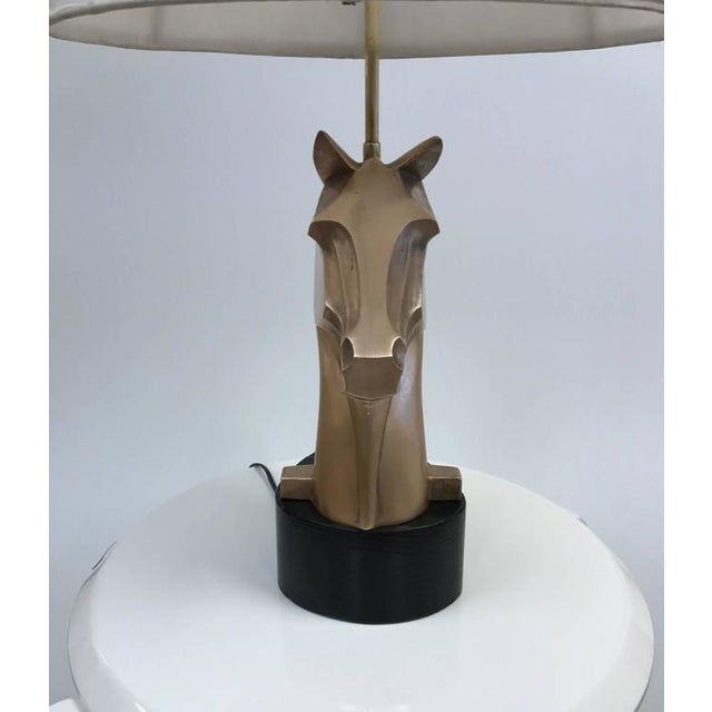 Pair of French, bronze horse lamps. Has a solid black lacquered wood base. Lamps are heavy and each weighs roughly ten...
