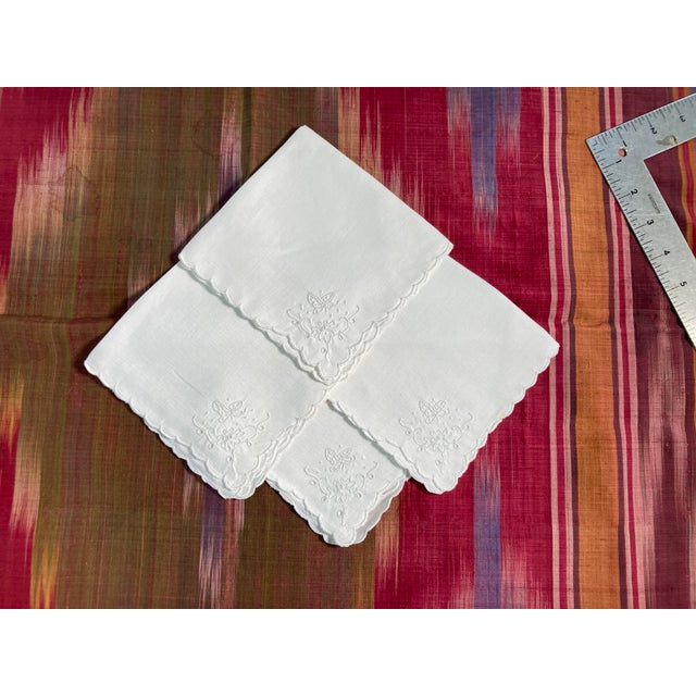 A set of 4 hand embroidered white on white linen napkins, starched pressed and ready to serve!