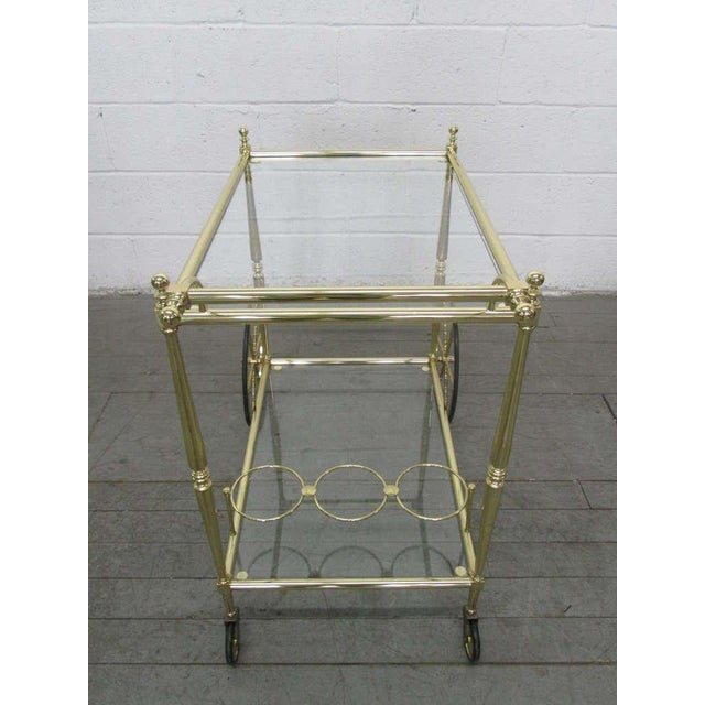 Lacquered brass bar cart with two glass top tiers. Has three compartments for bottles. Trolley