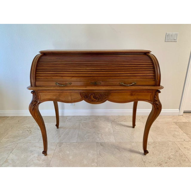 Rare 19th century French walnut roll top desk in the style of Louis XV. The tambour door locks with a key. Also finished...