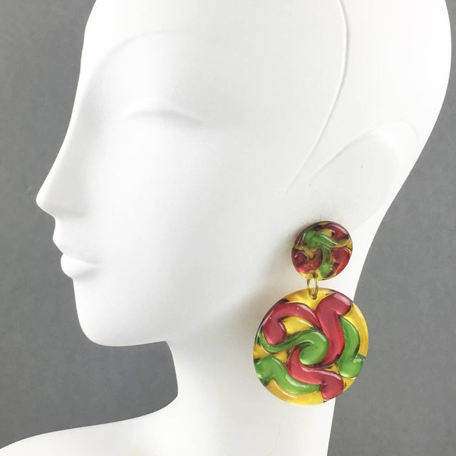 Lovely oversized Lucite clip on earrings. Huge disk dangling shape featuring dimensional carving with multicolor swirling....