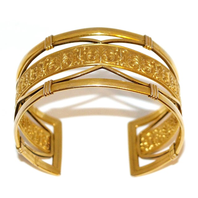 Circa 1930s to 1940s Krementz cuff with a heavy 14k gold overlay and an ornate motif covering the center strip. It has a...