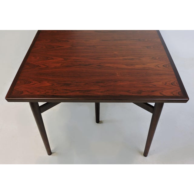 Elegant expandable dining or conference table in rosewood designed by Arne Vodder and manufactured in Denmark by Sibast....
