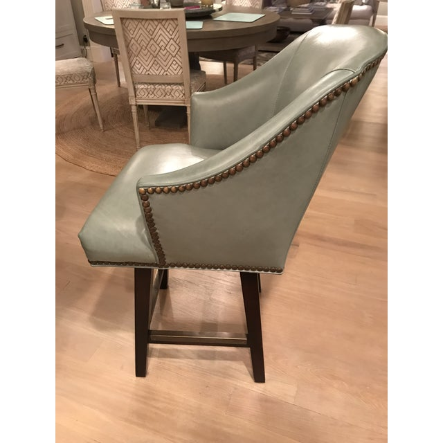 Very comfortable swivel counter stools, with full back, in celadon leather, with antique brass nail heads and kick plates,...