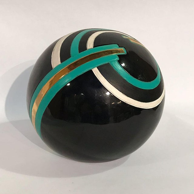 Striking ceramic orb with incised and colorful Art Deco-style embellishment. Believed to have been sold by Neiman Marcus...