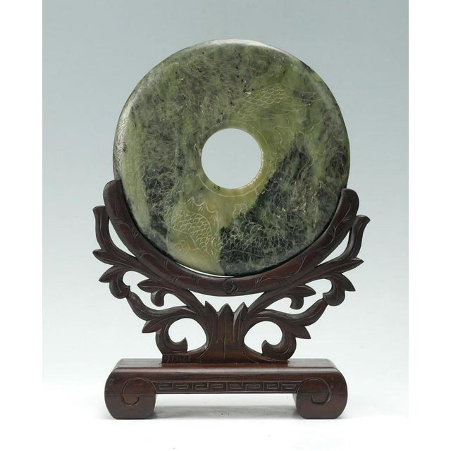 A large Chinese spinach green jade hard stone bi disc relief-carved on one side with mythical creatures. The other side...
