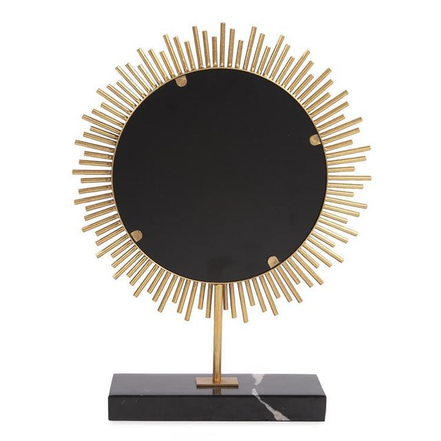 The Sunburst Table Mirror This table top mirror features a sunburst design of metal rods. The gold finish intensifies the...
