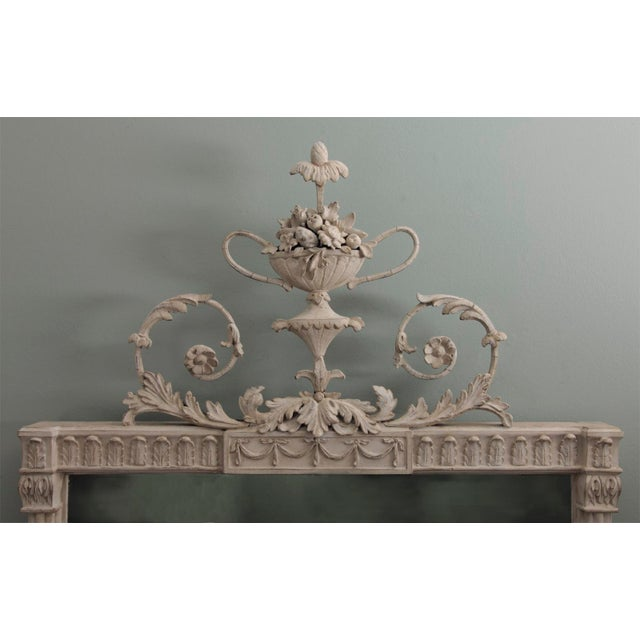 An antique English neoclassical mirror in the style of Robert Adam. The top cast composition foliate scroll ornament is...