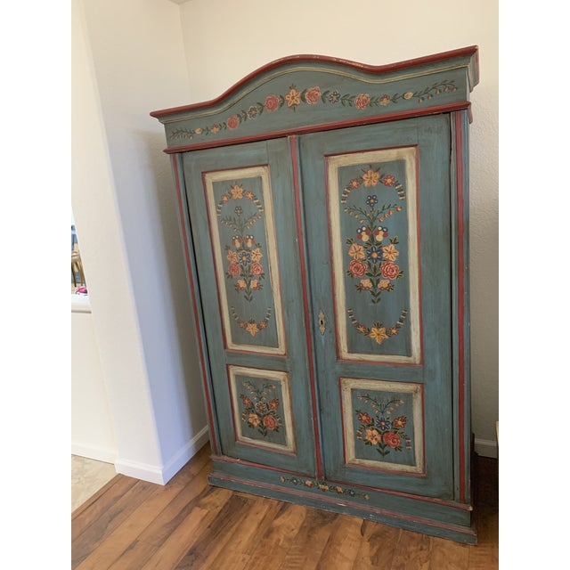 Rustic farmhouse antique hand painted wood armoire with floral motif. Interior shelf for linens, entertainment devices or...