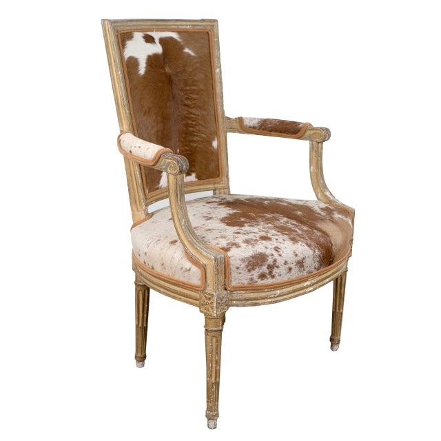 Beautiful pair of Louis XVI Fauteuil armchair upholstered in vintage cowhide, welting and carved frame. Chairs are in good...