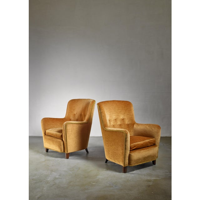 A pair of Danish easy chairs by Birte Iversen for cabinetmaker A.J. Iversen with a yellow velours, buttoned upholstery....