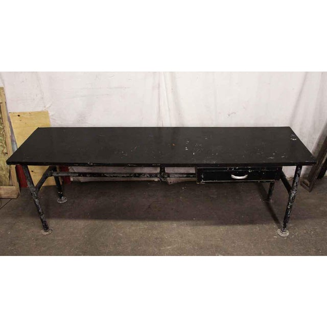 Industrial work table with a utility drawer and wooden surface. Please inquire for a refinishing option.